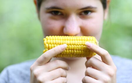 teenager girl eating boiled corn cob close up photo on green garden background Banco de Imagens - 127679695