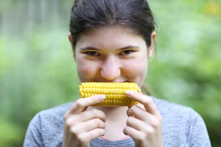 teenager girl eating boiled corn cob close up photo on green garden background