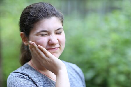 teenager girl with tooth ache close up photo on summer green garden background Banco de Imagens - 127679737