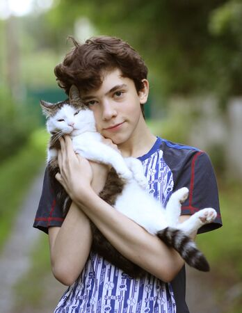 teenager boy with cat cuddle kiss hug on green garden background