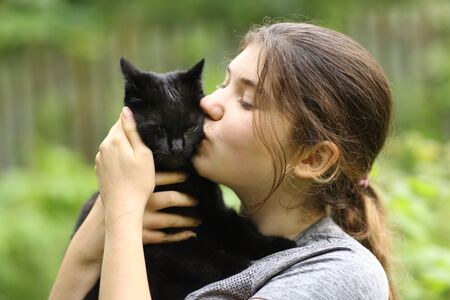 summer sunny photo of teenager girl hug cuddle kiss black cat close up outdoor photo