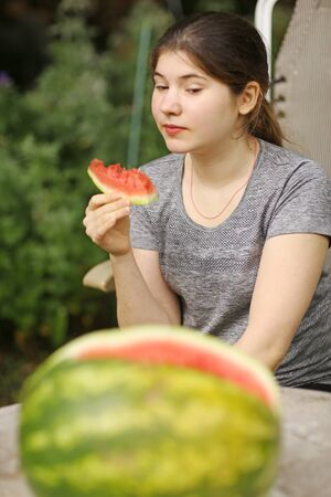 teenager girl eat cut water melon slice close up photo on green garden background Banco de Imagens