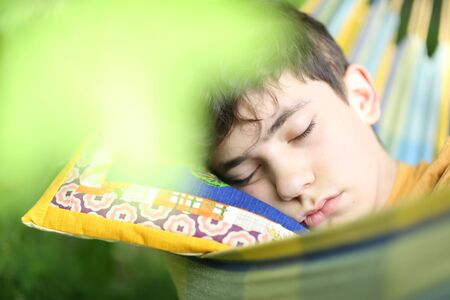 teenager boy resting sleep with book in hammock on summer green garden background 版權商用圖片