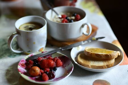 breakfast still life with oatmeal, seasonal berries, roasted toasts with lemon jam cup of tea spoon and knife close up horizontal photo 스톡 콘텐츠