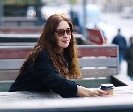 beautiful young woman in myopia correction glasses have cofe in street open air cafe close up portrait
