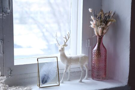 christmas deer vase and ikebana bouquet still life on windowsill with snow background