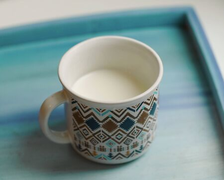 cup of milk stay on wooden painted tray close up photo