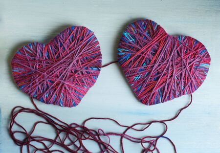 happy Valentines day still life card with woolen yarn thread heart , ball of thread and copy space on wooden painted board background