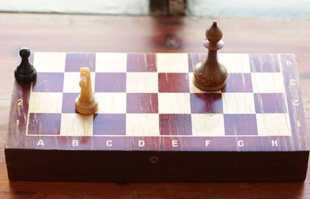 old retro chessboard with chess pieces knight queen pawn pieces close up photo