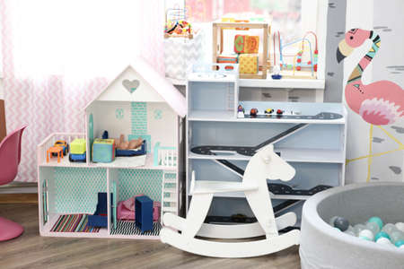 kid room interior coner with toys, cupboard, wooden hoarse and chair on window background 스톡 콘텐츠