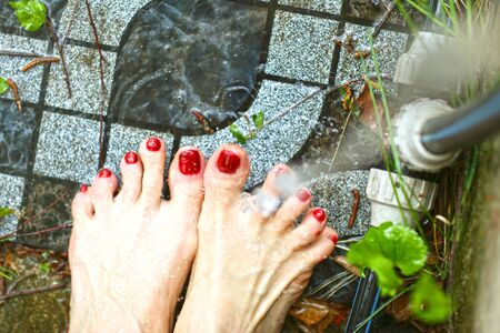woman feet with red nail lacquer washing with water pate on garden tale background
