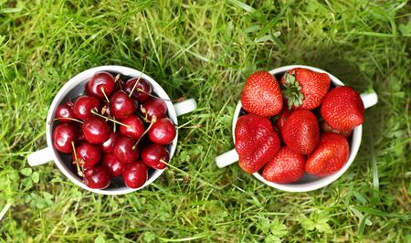 healthy breakfast - strawberries and sweet cherry in bowl close up photo on green grass background with copy space