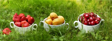 healthy food - strawberries and sweet cherry apricots fruit in bowl close up photo on green grass Stock Photo