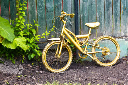 golden bicycle as a formal garden decoration on wooden blue fence background