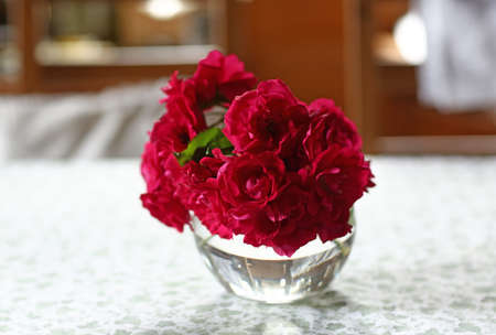 red roses in crystal vase on white table close up photo