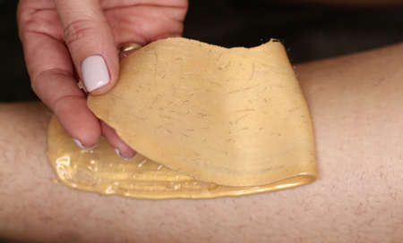 cosmetician hands make depilation procedure on woman legs with wax