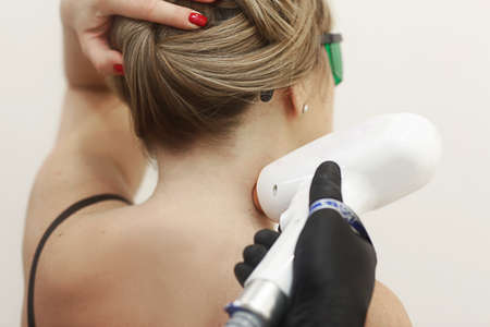 cosmetician hands make laser hair removal depilation procedure on woman neck closeup photo Standard-Bild