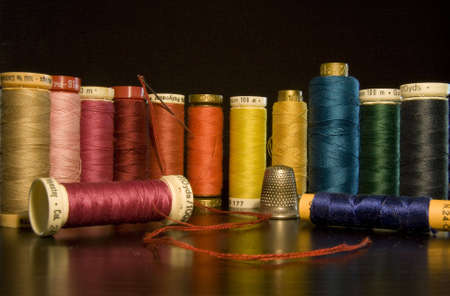 threading: colored threads to sew on black background Stock Photo