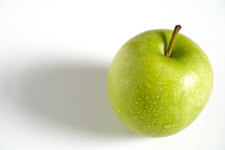 A whole granny smith green apple against a plain whit background