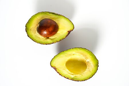 An avocado sliced in half to reveal the core against a plain whit background
