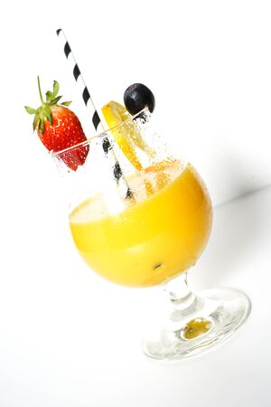 An orange cocktail drink with a party straw against a plain white background