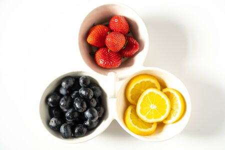 A serving dish filled with strawberries, lemon slices and black grapes against a plain white background Reklamní fotografie