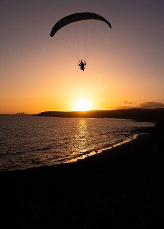 A sunset with a paraglider in the foreground Banque d'images