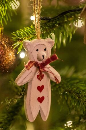 A white wooden bear shaped Christmas Tree Decoration hanging from a tree