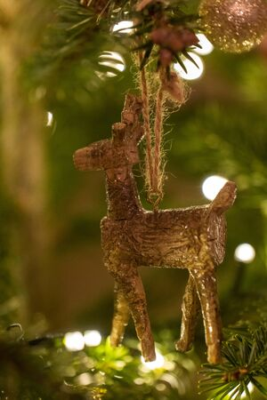 A wooden reindeer shaped Christmas Tree Decoration hanging from a tree 版權商用圖片