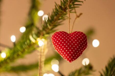 A fabric heart shaped Christmas Tree Decoration hanging from a tree 版權商用圖片