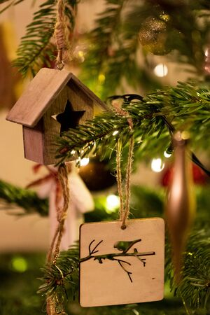A wooden house shaped Christmas Tree Decoration hanging from a tree