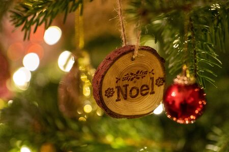 A Noel log shaped Christmas Tree Decoration hanging from a tree