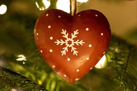 A red wooden heart shaped Christmas Tree Decoration hanging from a tree