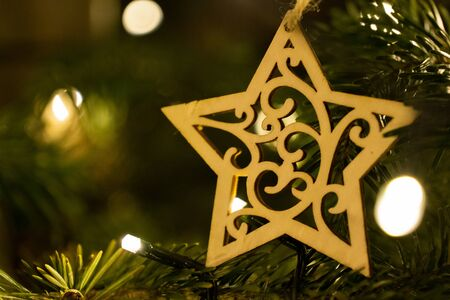 A wooden star shaped Christmas Tree Decoration hanging from a tree