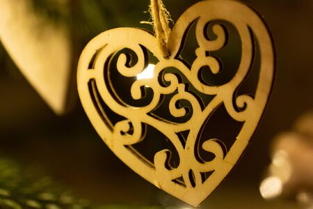 A wooden heart shaped Christmas Tree Decoration hanging from a tree