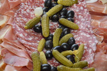 Zoom on a sausage plate with small gherkins and olives