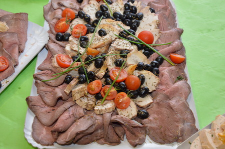 Zoom on a meat plate with tomatoes and olives