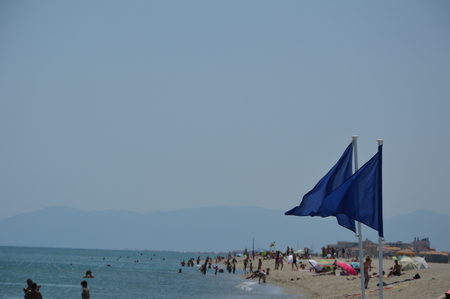 Blue safety flag on the beach Stock Photo