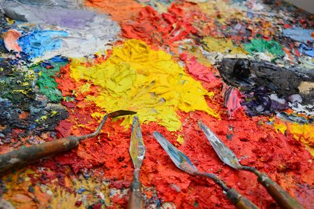 Zoom on a painter's palette in his workshop with tools 写真素材