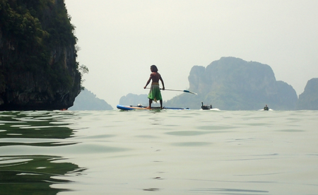 A man is floating on a board, standing, Thailand Stock Photo