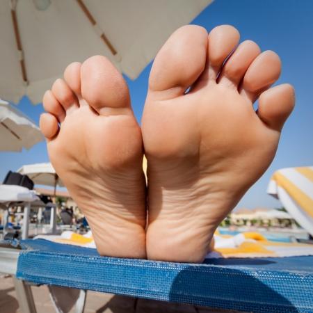 Groothoek close-up van een vrouw zolen op een strand stoel Stockfoto