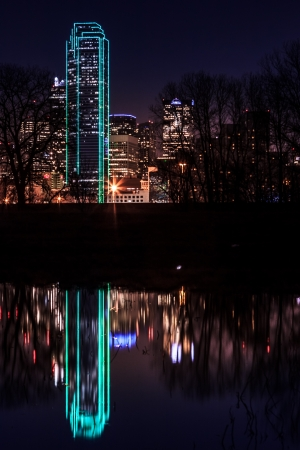 Dallas skyline - Bank of America building illuminated in green and reflected in a pond photo