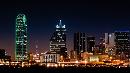 nightime: Dallas skyline by night with the Renaissance Tower in the middle and the Bank of America building illuminated in green
