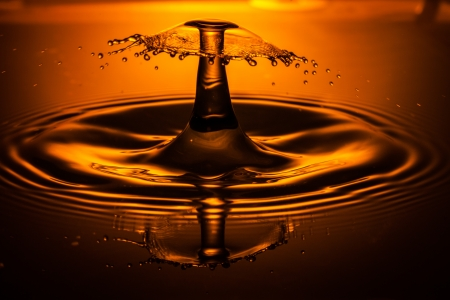 Orange water drop collision and splash frozen in motion Stock Photo
