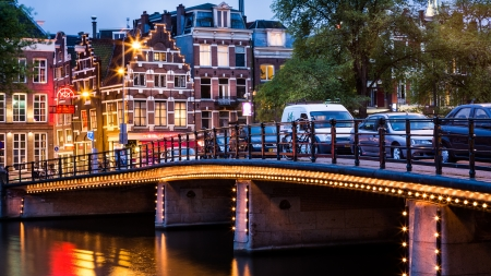 Halvemaans bridge from Amsterdam, illuminated, with typical dutch houses in the background