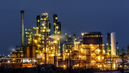 gas refinery: Closeup of an illuminated oil and gas refinery plant at night
