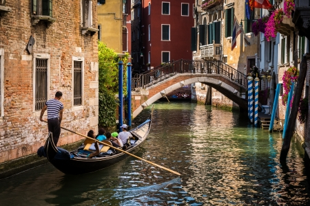 Gondola with tourists sailing on a water street in Venice Italy