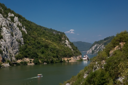 gorge: View over the Danube Gorges at the Serbian-Romanian border with a boat sailing towards a white church