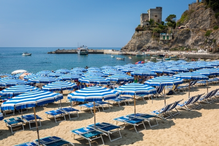monterosso: MONTEROSSO AL MARE, ITALY - JULY 23  Umbrellas and seats aligned on a sandy beach on July 23, 2013 in Monterosso al Mare, Italy
