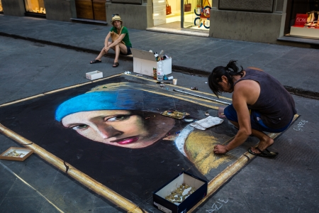 FLORENCE, ITALY - JULY 24  A street artist draws the Girl with a Pearl Earring, the famous Vermeer painting, on asphalt on July 24, 2013 in Florence, Italy  A tourist watches the creative process